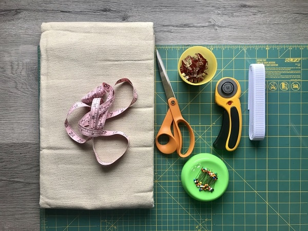 "Drop cloth, measuring tape, scissors, sewing clips, pins, rotary cutter, 1"" elastic sitting on cutting mat."