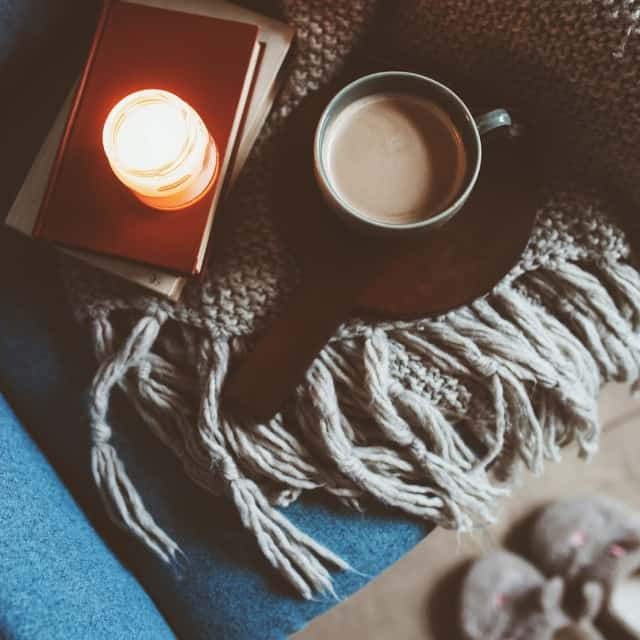 A coffee mug and books with lit candle sitting on blanket draped over a chair.