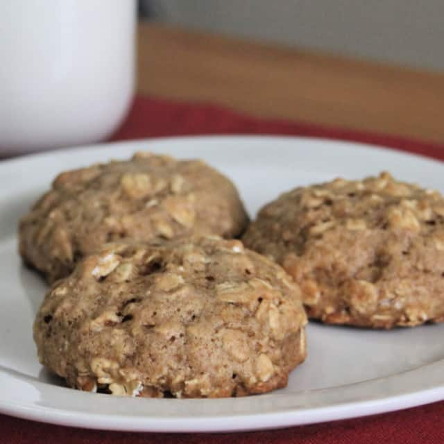 Applesauce cookies on a white plate with a glass of milk in background.
