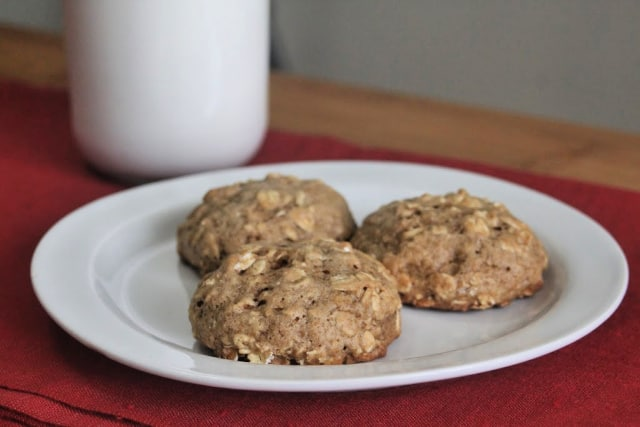 Applesauce oatmeal cookies on a plate with a glass of milk.