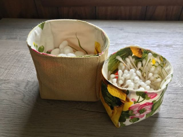 Two fabric baskets, one holding cotton balls and one holding cotton swabs.
