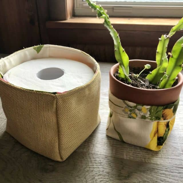 A fabric basket holding a roll of toilet paper sitting next to a potted plant in a floral fabric basket.