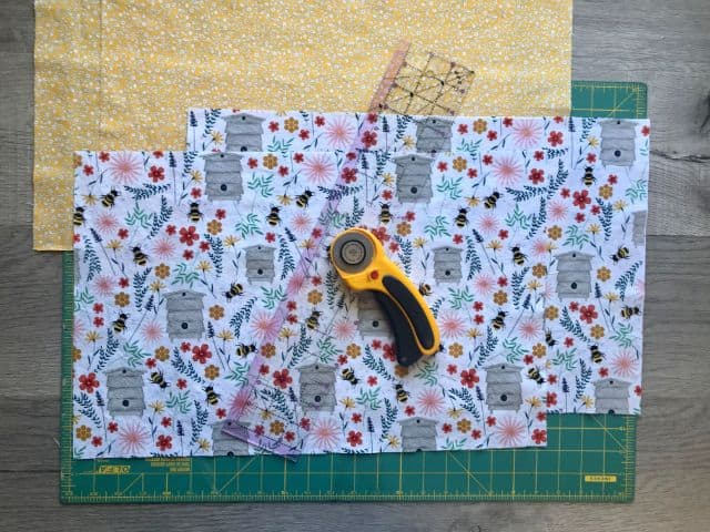 Two fabrics cut to size with rotary cutter and acrylic ruler