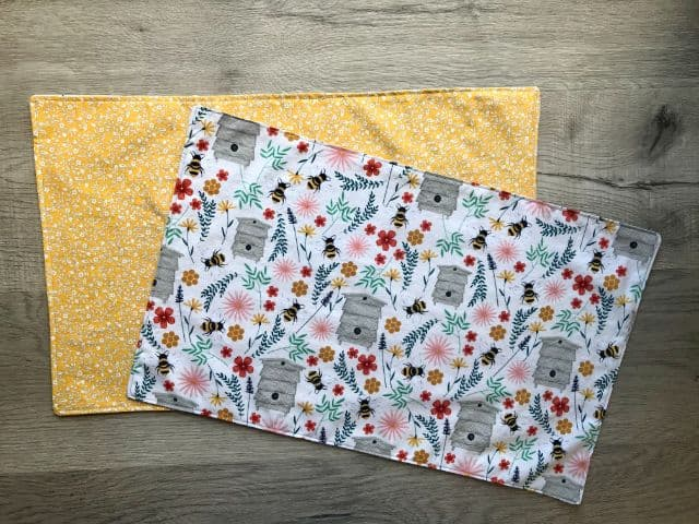 Two fabric placemats in different fabrics - one with mustard yellow flowers and the other with bees, flowers and foliage