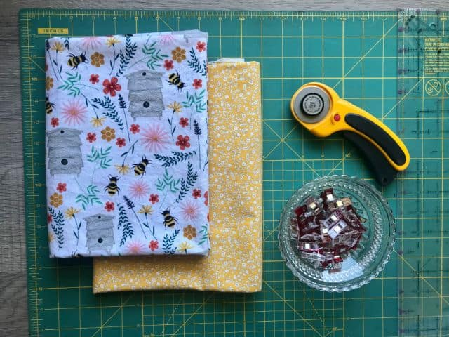 Two printed cotton fabrics, rotary cutter, sewing clips, acrylic ruler, cutting mat