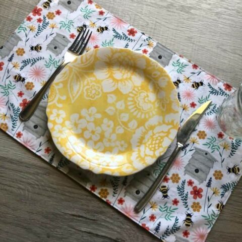 Fabric placemat featuring flowers and bees print with place setting