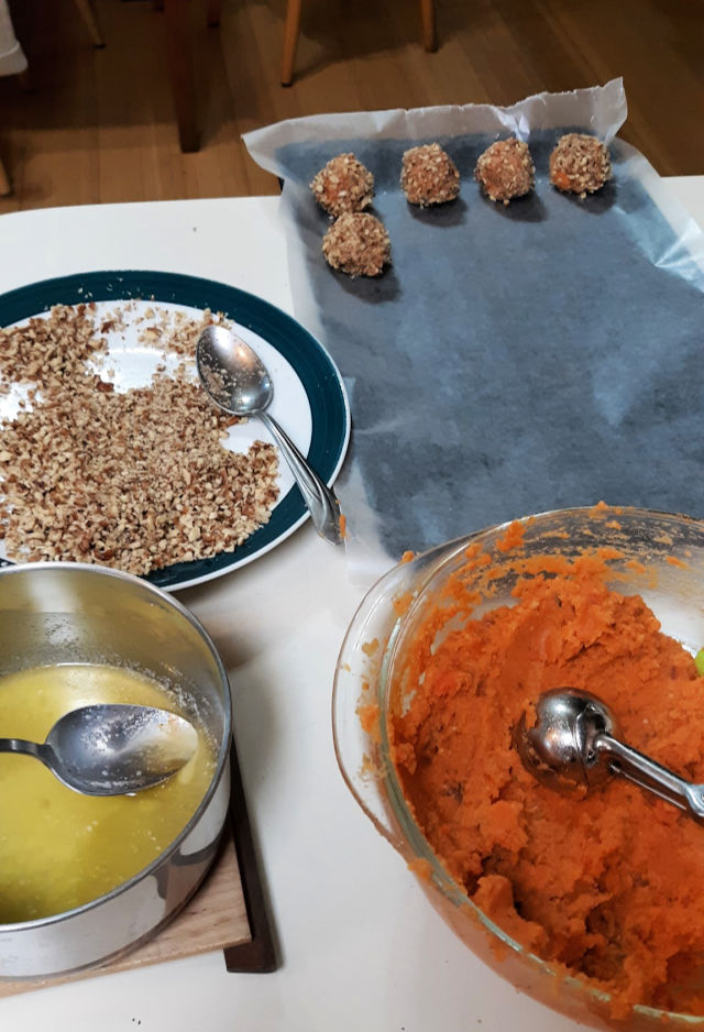 A counter top spread with abowl of mashed sweet potatoes, a pan of melted butter, a plate spread with chopped nuts and a wax paper lined baking sheet with sweet potato balls sitting on top.