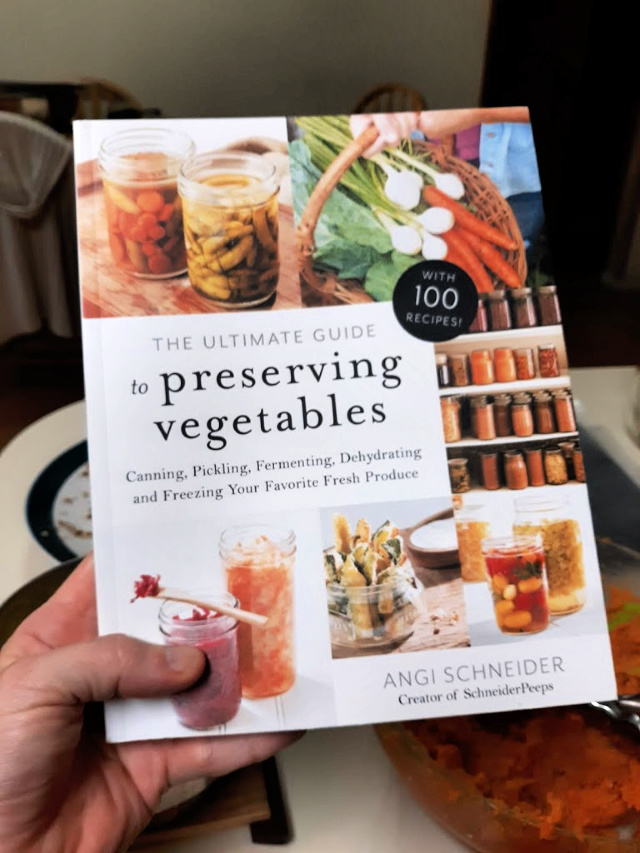 A woman's hand holding a copy of The Ultimate Guide to Preserving Vegetables book.