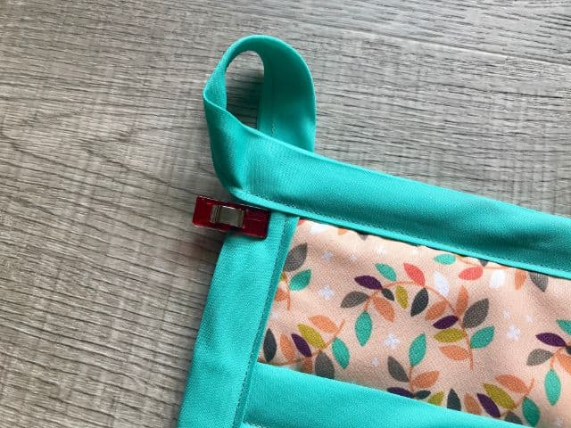 Bias tape tail turned into a loop and held to the back side of pot holder with a sewing clip