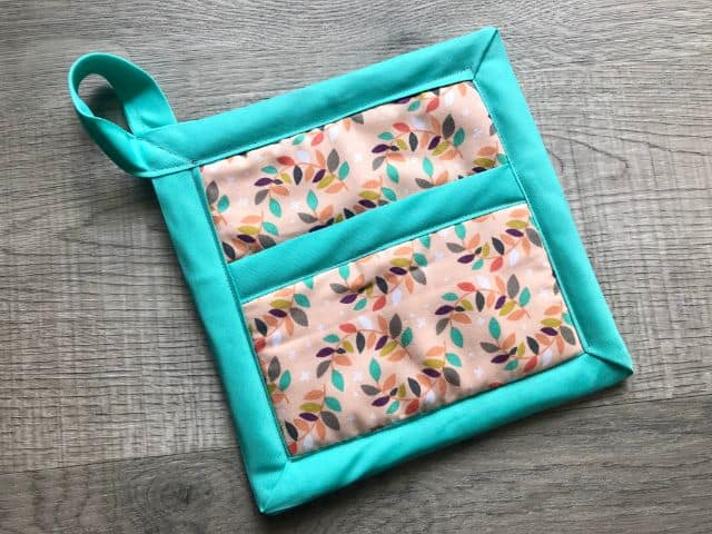 Completed hot pad with leaf print, teal bias tape and hanging loop