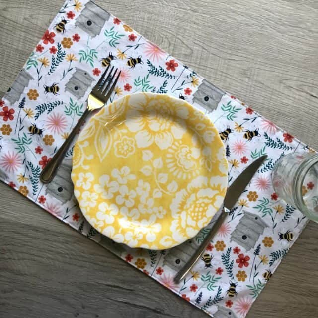 A placemat sitting with a plate, knife, and fork on top of it.