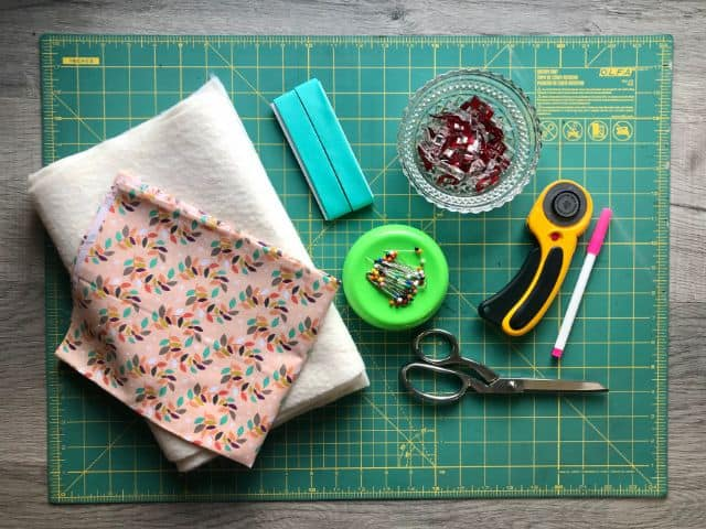 Flat lay of cutting mat, rotary cutter, fabric shears, sewing clips, straight pins, bias tape, fabric and batting