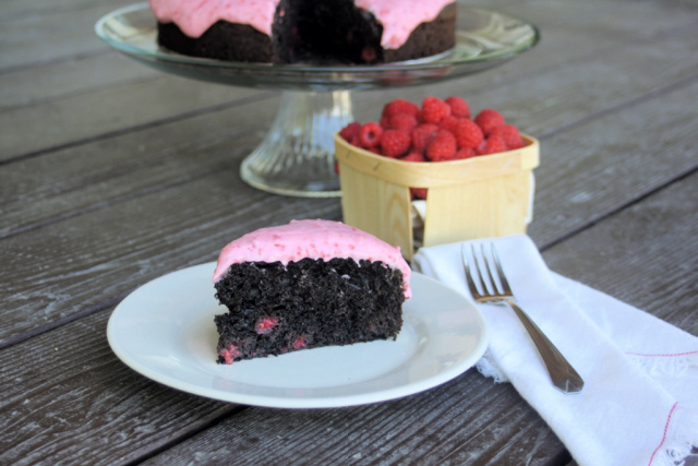 A slice of chocolate raspberry cake on a white plate with a napkin and fork sitting to the right - a basket of berries and rest of cake on glass cake plate behind it.