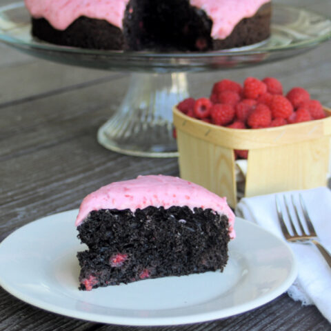 A slice of chocolate raspberry cake on a white plate with a napkin and fork sitting to the right in front of a basket of fresh berries and rest of cake on glass cake plate.