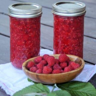 2 jars of raspberry pie filling sitting behind a wooden bowl full of fresh raspberries