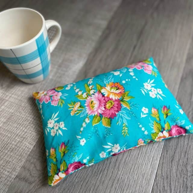 A floral rice-filled heating pad sitting on a table by a coffee cup.