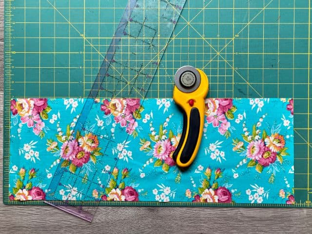 Teal floral fabric laying on cutting mat with rotary cutter and ruler