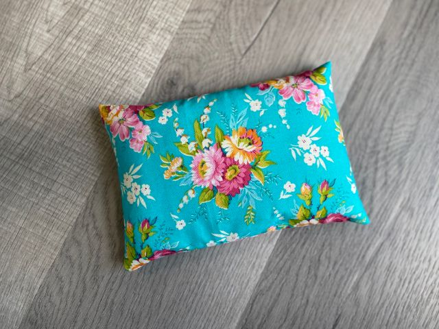 Teal floral fabric rectangle pouch filled with rice