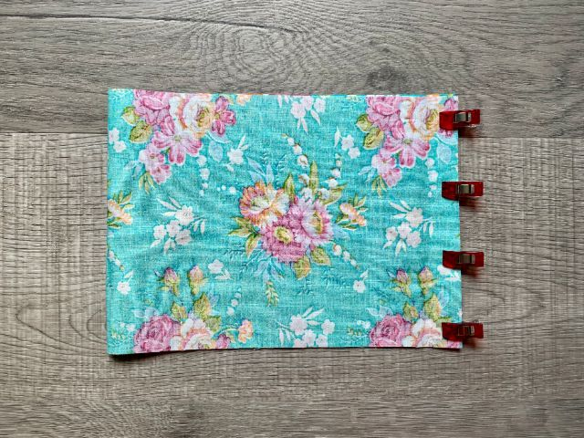 Teal floral fabric folded in half with sewing clips holding open end