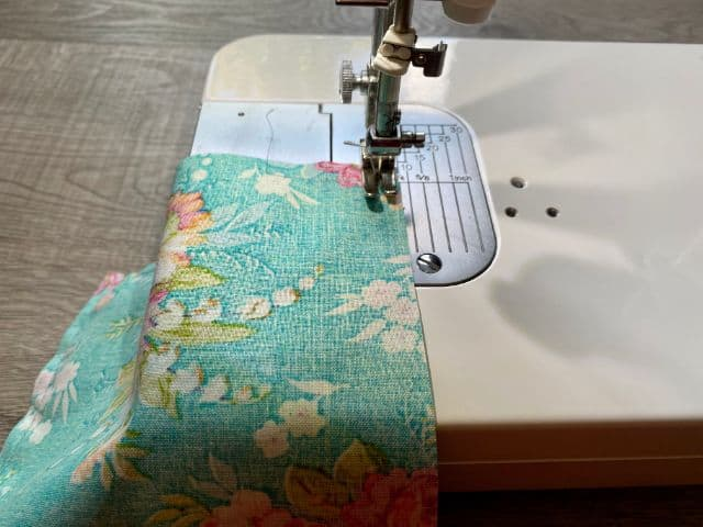 Sewing machine stitching teal floral fabric