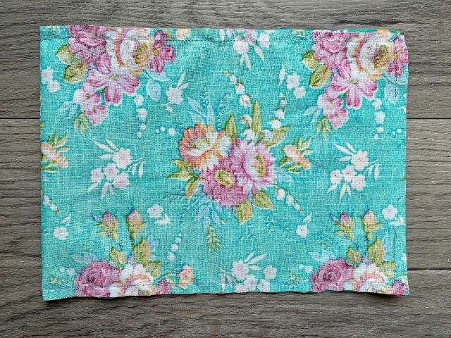 "Inside out rectangle of teal floral fabric sewn with 3"" opening at one end"