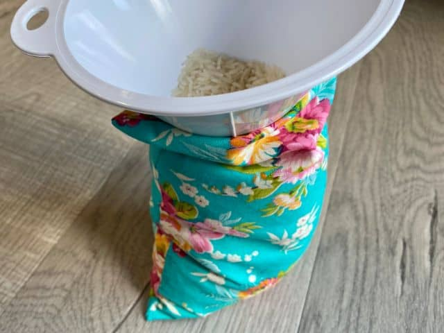 Funnel inserted in homemade heating pad being filled with rice