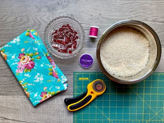 Floral fabric, sewing clips, magenta spool of thread, hand sewing needles, rotary cutter, cutting mat, bowl of rice