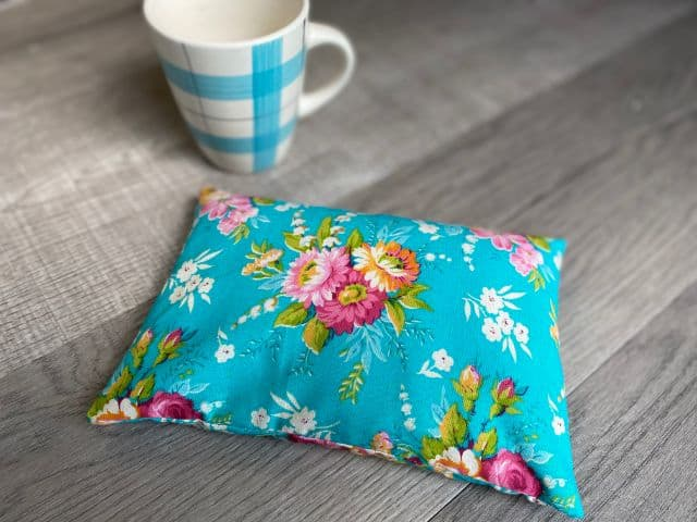 Teal floral fabric rectangle pouch filled with rice and coffee mug flat lay