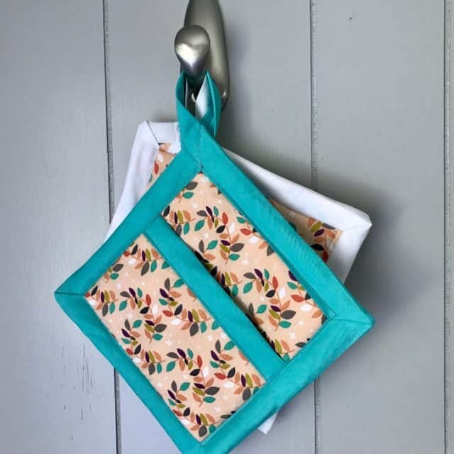 Pot holders hanging from a metal hook.
