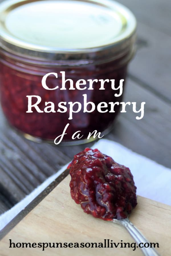 A spoon heaped with cherry raspberry jam on a wooden board with a sealed jar behind it with text overlay.