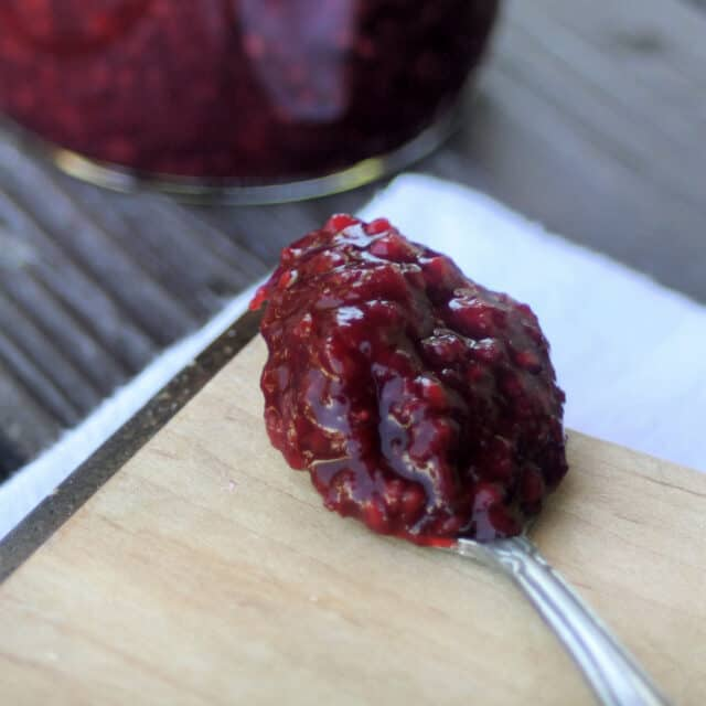 A spoon heaped with cherry raspberry jam sitting on a wooden board.