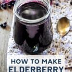An open jar of syrup sitting on a floral placement next to a spoon and surrounded by fresh elderberries with text overlay stating: how to make elderberry syrup.