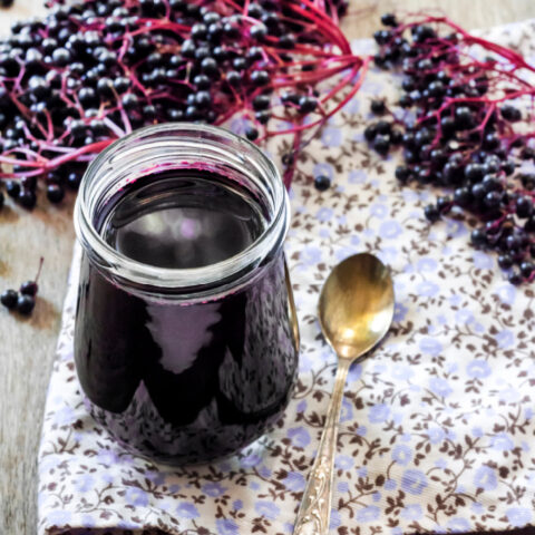 Elderberry syrup in an open glass jar sitting on a floral napkin next to a spoon surrounded by fresh elderberries on the stem.