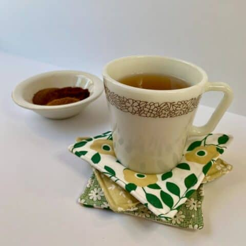Tea in white coffee mug setting on three fabric mug rugs with a bowl of spices in background