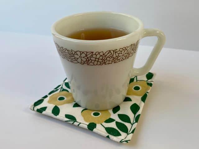 White mug of tea setting on green flowered mug rug