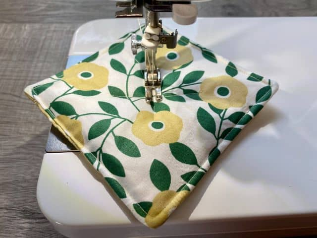Floral mug rug on sewing machine plate with needle in center
