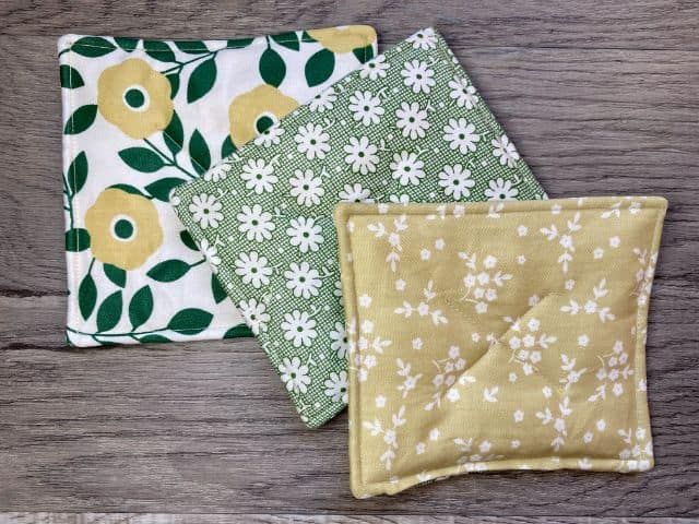 Three fabric mug rugs in white and green floral fabric