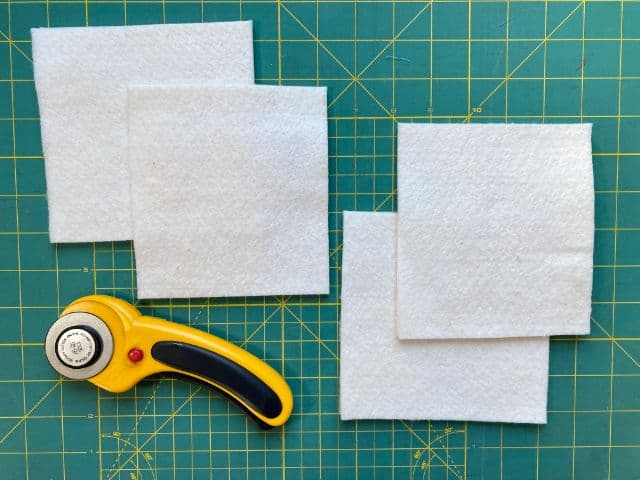 Four squares of batting on cutting mat with rotary cutter