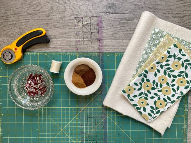 Flat lay of cutting mat, rotary cutter, sewing clips, thread, ruler, spices, batting and fabric