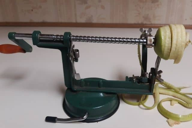 An apple being peeled, cored, and sliced on a green hand crank machine.