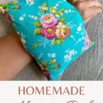 A blue floral heating pad sitting on a woman's wrist with text overlay stating: Homemade Heating Pad.