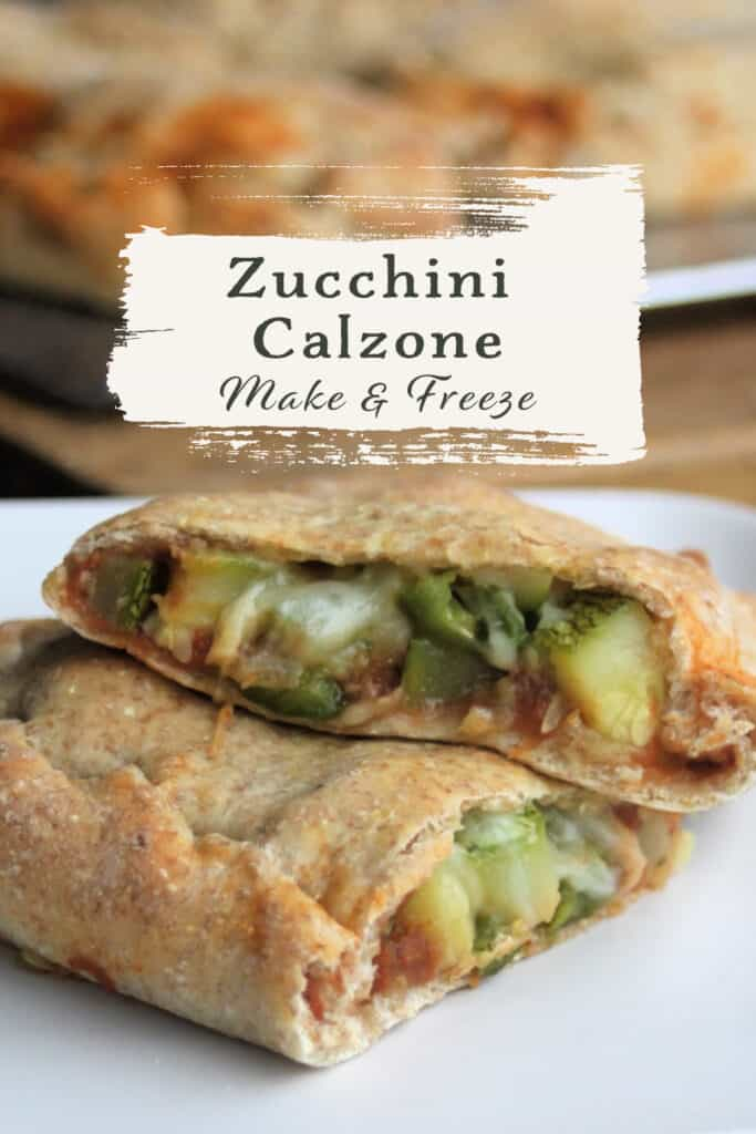 A zucchini calzone sliced in half exposing the vegetables inside the dough on a white plate with text overly stating zucchini calzone make & freeze.