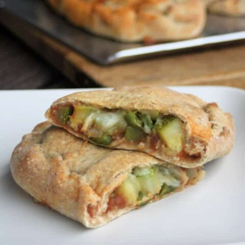 A zucchini calzone sliced in half exposing the vegetables inside the dough on a white plate.