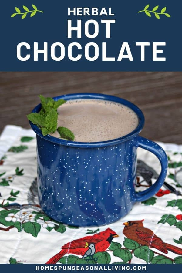 A blue tin cup full of hot chocolate decorated with fresh sprigs of mint sitting on a floral and bird covered placemat with text overlay stating: herbal hot chocolate.