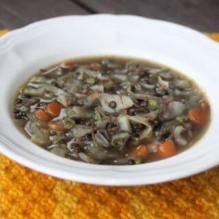 A white bowl full of cabbage lentil soup sitting on an orange table runner.