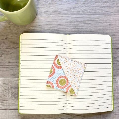 Mug and open book with square fabric corner bookmark laying in center