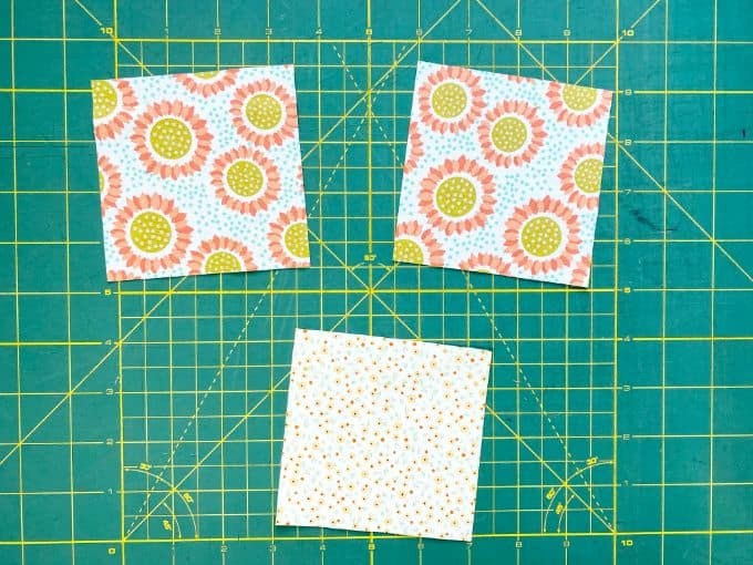 4 x 4 fabric squares with flowers on green cutting mat
