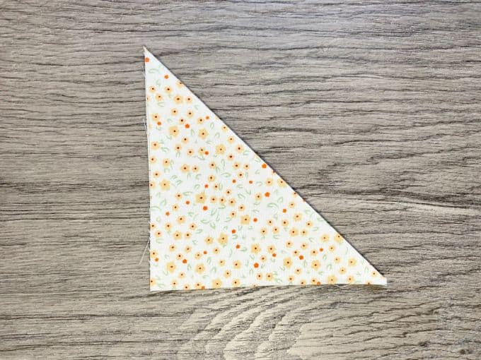 Square of fabric folded in half to make a triangle