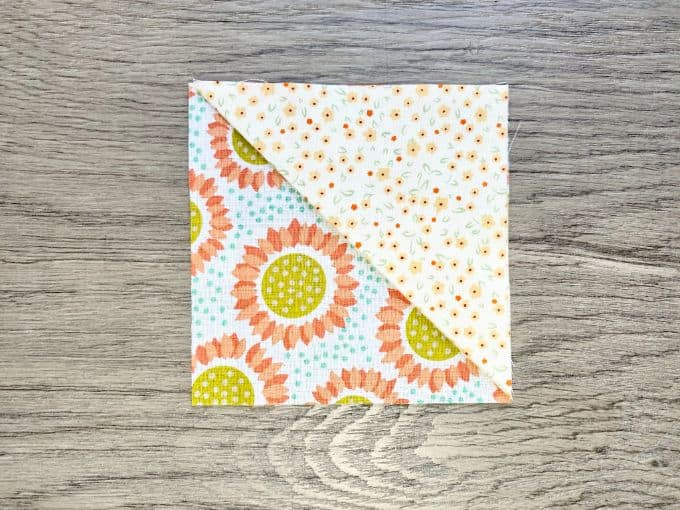 Square flowered fabric with triangle of fabric aligned at one corner