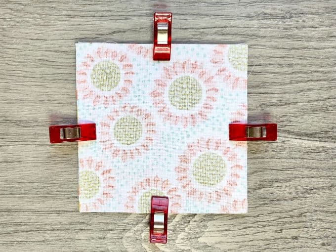 Fabric squares stacked with right sides together and clipped on all four sides with red sewing clips